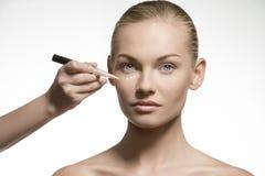 应用在她的脸的自然妇女化妆用品 免版税库存图片