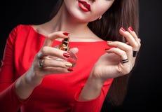 应用在她的腕子的妇女香水在黑背景 免版税图库摄影