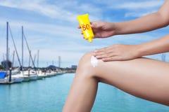 应用在她的腿的妇女遮光剂有靠码头的迷离小船的 库存照片