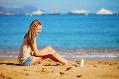 应用在她的腿的美丽的妇女遮光剂 免版税库存图片
