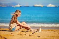 应用在她的腿的美丽的妇女遮光剂 图库摄影