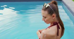 应用在她的身体的比基尼泳装的妇女遮光剂化妆水在游泳池边4k附近 股票录像