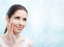 应用在她的面孔的妇女奶油-冬天脸面护理 免版税库存照片