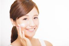 应用在她的面孔的少妇化妆奶油 库存照片
