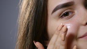 应用在她的面孔的年轻美丽的妇女奶油,隔绝在灰色 影视素材