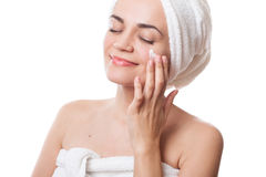 应用在她的面孔的毛巾的女孩奶油在浴以后 免版税库存图片
