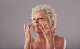 应用在她的面孔的美丽的老妇人润肤霜 图库摄影