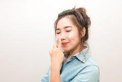 应用在她的面孔的年轻亚裔妇女润湿的奶油 免版税库存照片