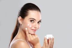 应用在她的面颊的美丽的少妇一些面部奶油 免版税库存图片