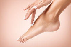 应用在她美好的脚的妇女奶油 免版税库存图片