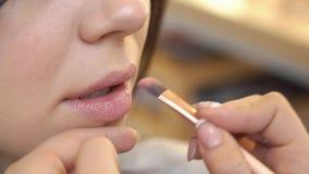 应用在客户的嘴唇的专业化妆师唇膏美容院的 秀丽、脸和时尚概念 影视素材
