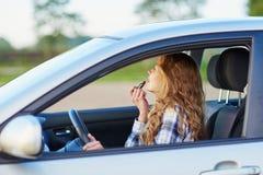应用在汽车的妇女唇膏,当驾驶时 免版税库存照片