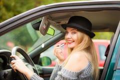 应用在汽车的年轻女人唇膏 免版税库存照片