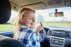 应用在汽车的美丽的妇女唇膏,当驾驶时 免版税图库摄影