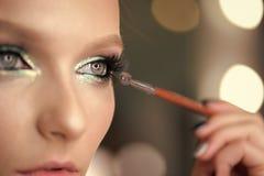 应用在睫毛的妇女黑染睫毛油有构成刷子的 申请在眼睛的年轻美丽的妇女染睫毛油构成  免版税图库摄影