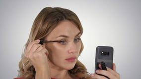 应用在睫毛的妇女黑染睫毛油看在她的在梯度背景的电话 免版税库存图片