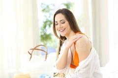 应用在肩膀的女孩遮光剂在旅馆客房 免版税库存照片