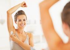 应用在腋下的微笑的妇女路辗防臭剂在卫生间里 免版税库存照片