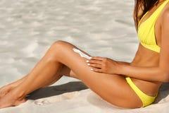 应用在腿的妇女sunblock奶油在海滩 t 化妆用品 免版税库存图片