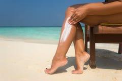 应用在腿的妇女sunblock奶油在美丽的热带海滩 免版税库存图片