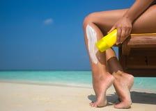 应用在腿的妇女sunblock奶油在美丽的热带海滩 图库摄影