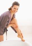 应用在腿的微笑的少妇奶油在卫生间里 免版税库存图片