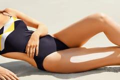 应用在腿的美丽的妇女特写镜头晒黑化妆水在海滩 免版税库存图片