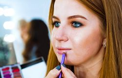 应用在逗人喜爱的年轻红色头发妇女的嘴唇的特写镜头女性手唇膏使用特别刷子 免版税库存图片