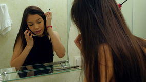 应用在镜子前面的俏丽的妇女染睫毛油睫毛,当谈话通过智能手机在卫生间里时 股票视频