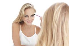 应用在镜子isol的ront的美丽的白肤金发的妇女染睫毛油 库存图片