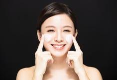 应用在面孔的妇女化妆水奶油 免版税图库摄影