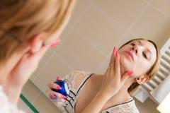 应用在面孔的妇女奶油 免版税图库摄影