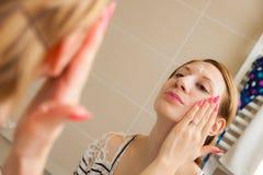 应用在面孔的妇女奶油 免版税库存图片