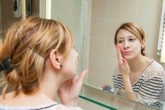 应用在面孔的妇女奶油 免版税库存照片