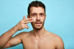 应用在面孔的年轻英俊的快乐的有胡子的人奶油色化妆水 免版税图库摄影