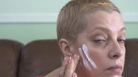 应用在面孔的成熟妇女面霜,当看照相机时 概念皮肤护理 股票录像