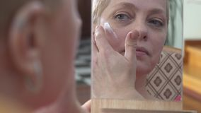 应用在面孔的成熟妇女面霜,当看镜子时 股票录像