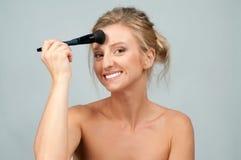 应用在面孔的美丽的妇女干燥化妆用品使用构成刷子 免版税库存照片