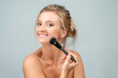 应用在面孔的美丽的妇女干燥化妆用品使用构成刷子 免版税库存图片