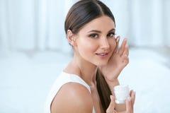 应用在面孔皮肤的妇女面霜在白色内部 免版税库存图片