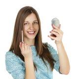 应用在面颊的年轻美丽的妇女粉末与刷子 免版税库存图片