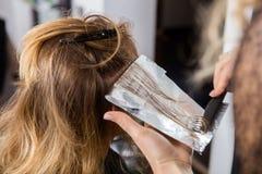 应用在顾客的头发的美发师染料在沙龙 图库摄影