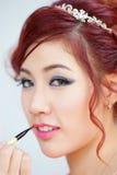 应用在嘴唇的秀丽妇女唇膏有刷子的。 免版税库存图片