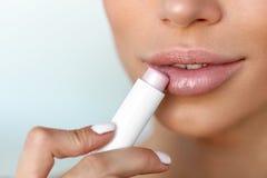 应用在嘴唇皮肤的美丽的妇女嘴唇保护者 beauvoir 免版税库存图片