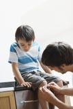 应用在他的儿子的膝盖的人绷带 免版税库存照片