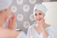 应用基础或润肤霜在她的面孔的年轻亚裔妇女 图库摄影
