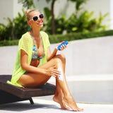 应用太阳保护化妆水的Tan妇女在游泳池附近 图库摄影