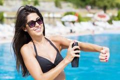 应用太阳保护奶油的美丽的微笑的妇女 免版税库存照片