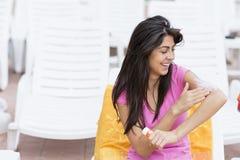 应用太阳保护奶油的美丽的微笑的妇女 库存照片