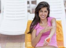 应用太阳保护奶油的美丽的微笑的妇女 图库摄影